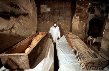 An archaeologist  stands near an intact sarcophagus inside the tomb TT33 in Luxor