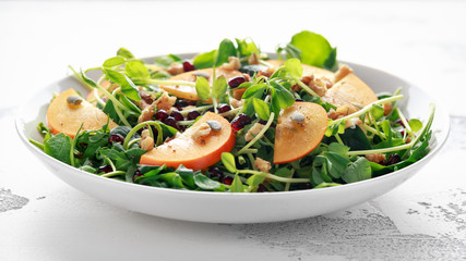 Tasty Persimmon and pea shoot salad with walnuts, pomegranate and pumpkin seed.