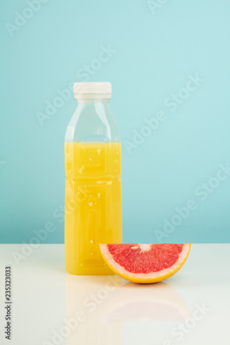 Orange drink and slice of grapefruit on white and blue