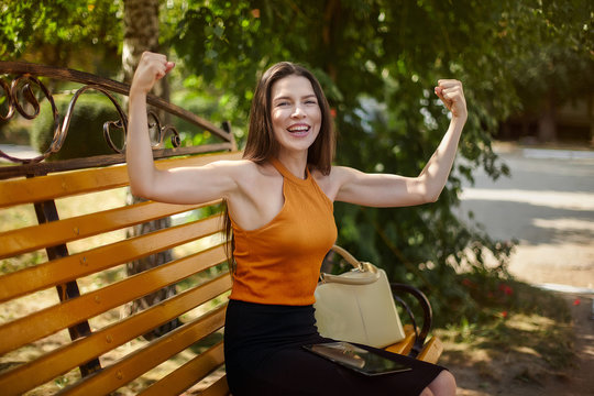 Joyful and happy business woman shows gestures with power. Hands up, sport and business.