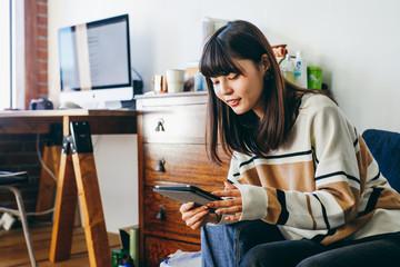 ソファーでくつろぎながらタブレットを使用する女性
