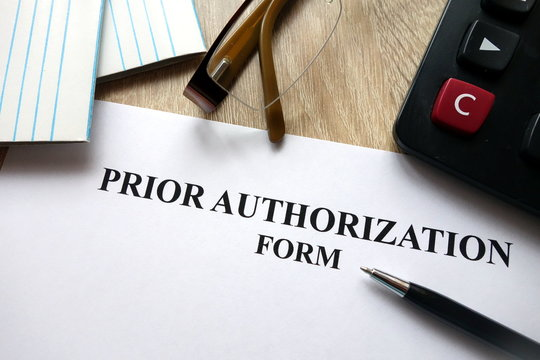 Prior authorization form with pen, calculator and   glasses on desk