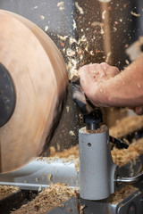 rotating piece of wood and fyling sawdust while making a bowl