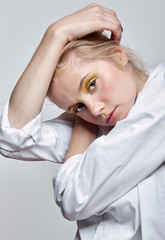 Portrait of a young blonde woman in white blouse on gray background