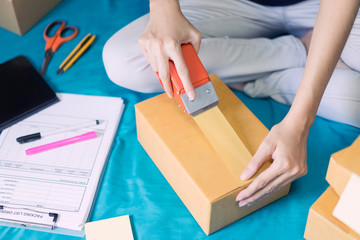 Woman holding pack machine, sealing cardboard boxes, check packing list order and delivery to customer on the bed, Shopping online.