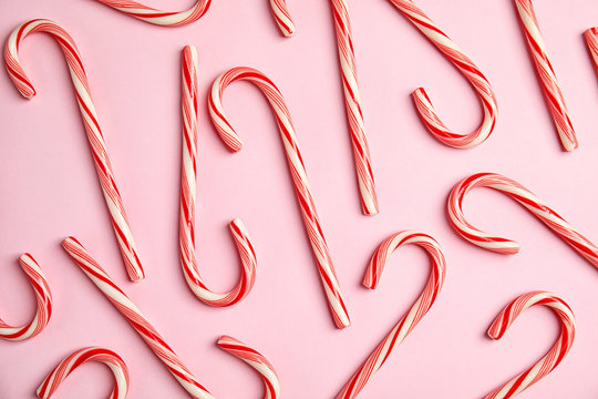Flat lay composition with tasty candy canes on color background