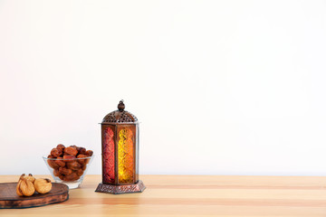 Muslim lantern Fanous and dried fruits on table against light background. Space for text