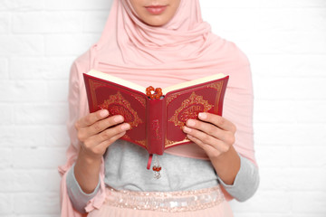 Young Muslim woman reading Koran against brick wall, closeup