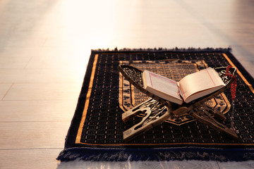 Rehal with open Quran and Muslim prayer beads on rug indoors. Space for text Wall mural