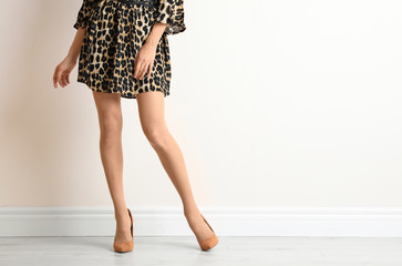 Young woman with beautiful long legs in stylish outfit near white wall, closeup. Space for text Wall mural