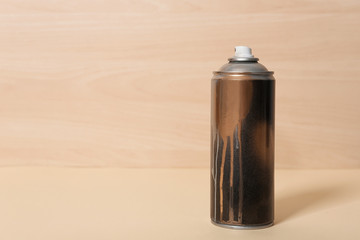 Used can of spray paint on wooden background. Space for text