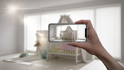 Hand holding smart phone, AR application, simulate furniture and interior design products in real home, architect designer concept, blur background, white scandinavian nursery