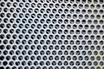 Metal plate with round holes. Honeycombs. Background image or texture of a hole in metal