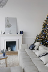 luxury apartment  decorated for New Year with white walls, christmas tree with gold and blue bolls, fireplace, dark blue velvet style chair