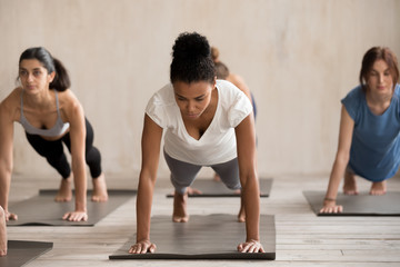 Group of diverse young sporty people doing yoga Plank pose, Push ups or press ups exercise, working...