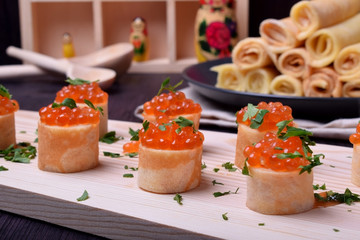 Crepes with red caviar on a wooden board sprinkled with parsley. Russian cuisine