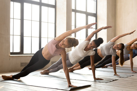 Group of young diverse sporty people doing yoga Vasisthasana exercise, Side Plank pose, working out, indoor full length, mixed race female students training at club or studio. Well being, wellness