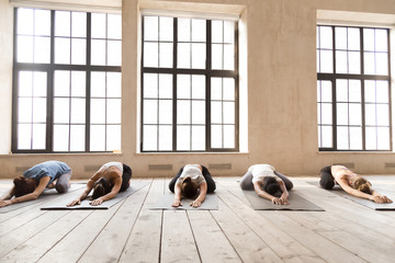 Group of young diverse sporty people practicing yoga lesson, doing Child exercise, Balasana pose, full length, mixed race students working out at club, white yoga studio. Well being, wellness concept