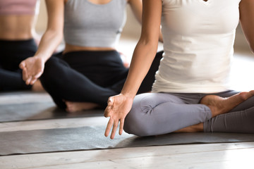 Yogi black woman and group of people doing yoga Padmasana exercise, Lotus pose with mudra, working out indoor close up, mixed race female students training at yoga studio. Well being, wellness concept