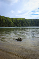 beautiful lagoon surrounded by mountains with a small rock in the medium. Ancient volcano crater. Seven Cities lagoon Azores Islands Portugal