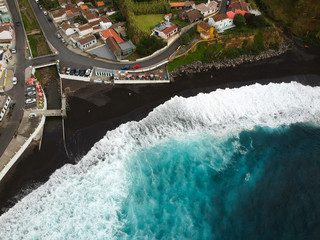 Aerial top view of sea waves hitting a beach with black volcanic sand with turquoise sea water. Seascape in the Portuguese coastline. Mosteiros village Azores islands. Drone shot.