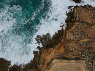 Aerial top view of sea waves hitting black volcanic rocks on the coastline with turquoise sea water. Amazing rock cliff seascape in the Portuguese coastline.