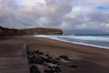 beach with black volcanic sand with turquoise sea water. Seascape in the Portuguese coastline. Azores islands.