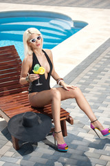 Beautiful sensual blonde with fashionable sunglasses relaxing at swimming pool with a juice. Attractive long fair hair woman in black low-cut swimsuit lying on sunbed, sexy summer shot.