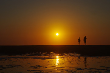 Silhouette of a couple walking on the beach, sunset in the background. Beautiful beach sunset. Holiday happiness.