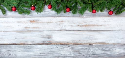 Christmas evergreen branches and red ornaments on white vintage wooden planks