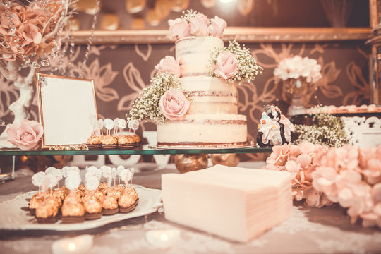 Luxury candy bar with huge arrenge of  desserts and candies, wedding cake