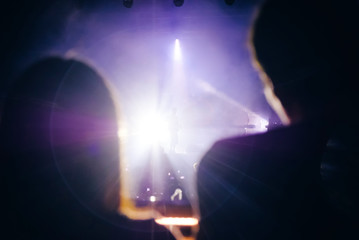 Singer silhouette beside the crowd of people at music concert. Bright stage lights. Couple watching a show from vip zone