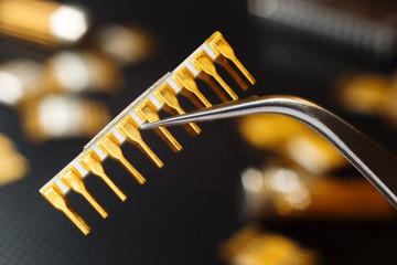 Golden microcircuit with tweezers on the background of electronic components.