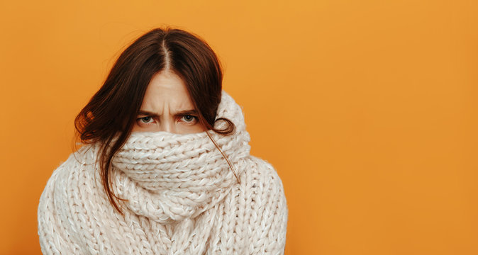 Cough and cold. Health. Woman portrait. Girl is looking from under her knitted scarf, on an orange background