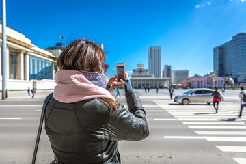 Ulaanbaatar, Mongolia - Sept 8th 2018 - A tourist taking a picture of the Sukhbaatar Square in a blue sky day in Ulaanbaatar, capital of Mongolia