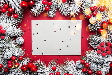 Merry Christmas and Happy Holidays greeting card. New Year. Noel. Silver, white and red Christmas ornaments and fir tree on red background top view. Winter holiday xmas theme. Envelope.
