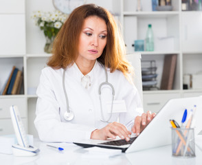 Doctor female in uniform is working behind laptop with documents
