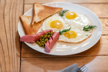 Breakfast food. American style breakfast with fried eggs, sausage, green peas and toast. The concept of a healthy morning.