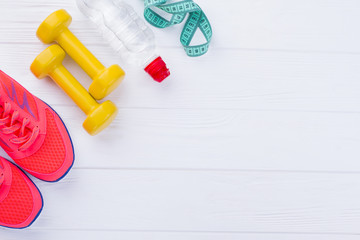 Fitness equipment with copy space. Sport shoes, dumbbells, bottle of water and measuring tape on white wooden background.