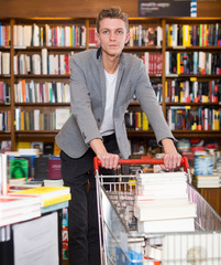 Positive man with cart searching for books