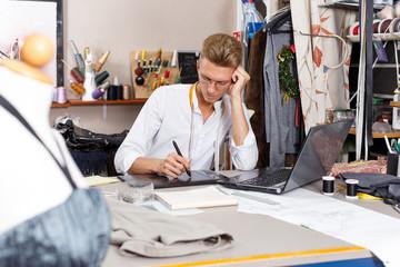 Tailor creating pattern using laptop