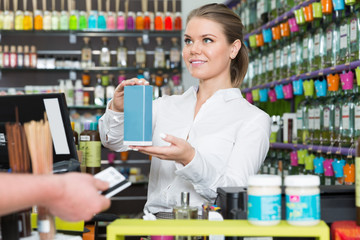 Salesgirl taking credit card while serving consumer in perfume shop