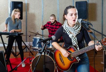 Attractive female soloist playing guitar and singing with her music band in sound studio