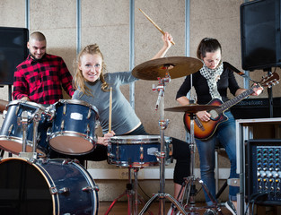 Music band with smiling girl drummer rehearsing