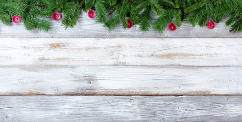 Christmas evergreen branches and red candles on white vintage wooden planks