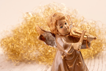 Angel with violin in front of golden hair on white wood as Christmas background