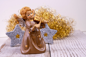 Angel with violin in front of golden hair and silver stars on white wood as Christmas background