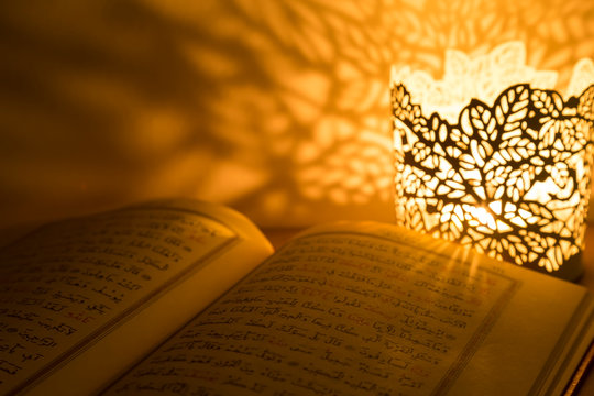 Quran and rosary beads on the white background with light lantern or candle for Islamic concept. Holy book Koran for Muslims holiday, Ramadan,blessed Friday message and three months