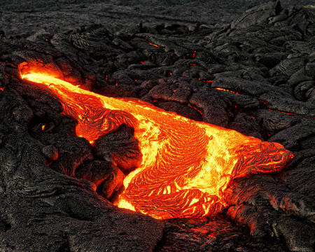 """Hot magma escapes from an earth crevice as part of an active lava flow, the glowing lava slowly cools and freezes - Location: Hawaii, Big Island, volcano """"Kilauea"""""""