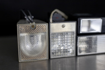 Old flash lamps on a metal table. Photo accessories from central europe.